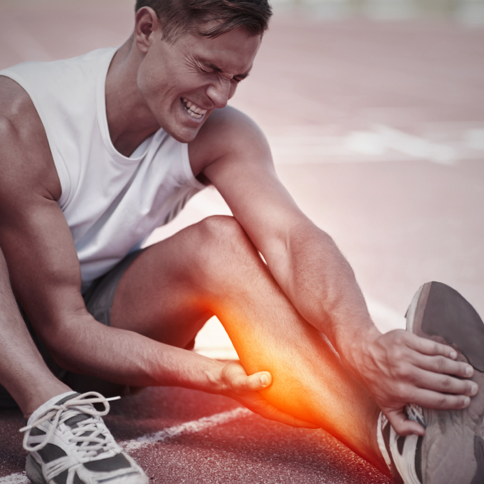 Shot of a young athlete holding his leg in pain