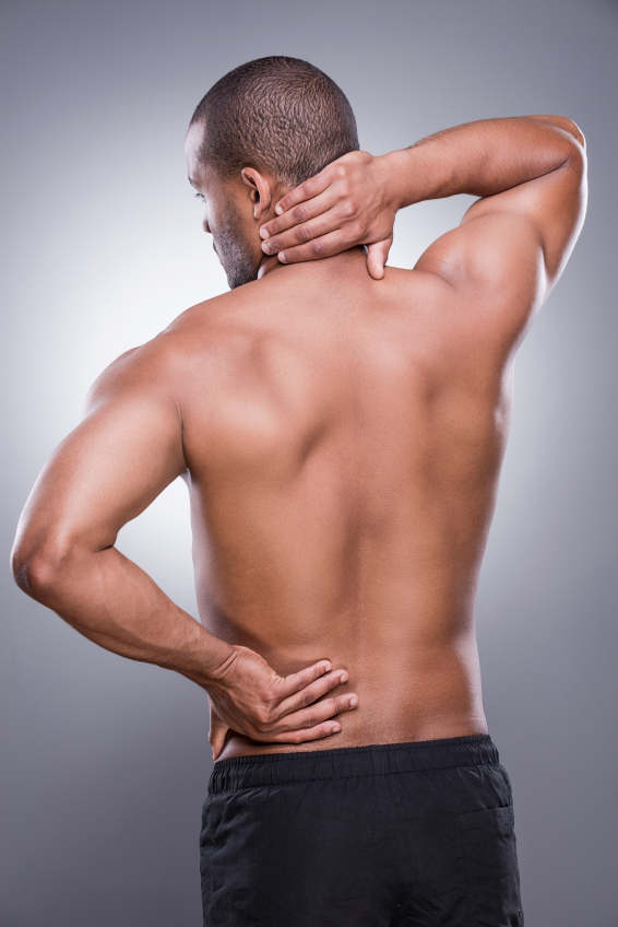 Feeling discomfort. Rear view of young muscular African man touching his hip and neck while standing against grey background