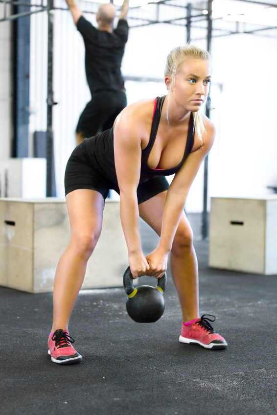 Attractive young woman lift kettlebells at fitness gym center. Man train hangups in the background.